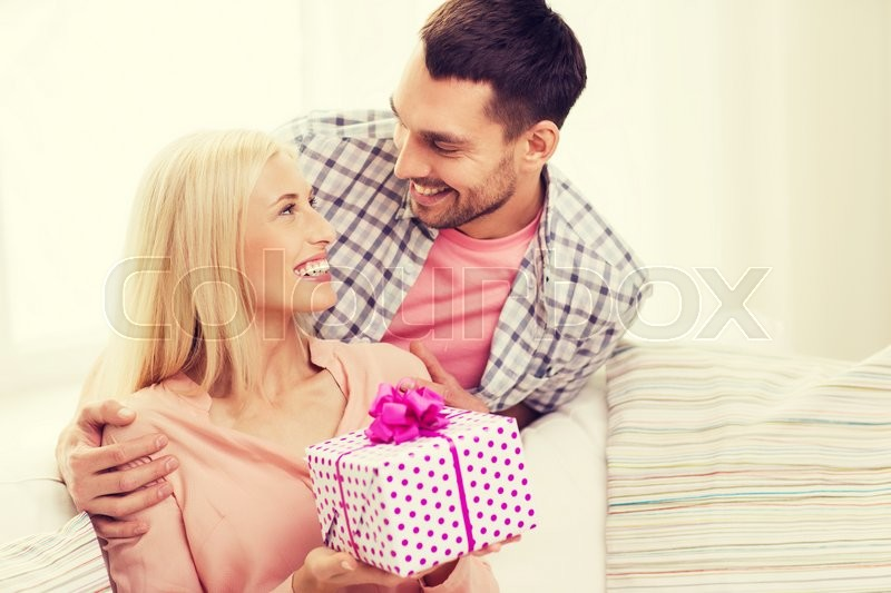 Stock image of 'relationships, love, people, birthday and holidays concept - happy man giving woman gift box at home'