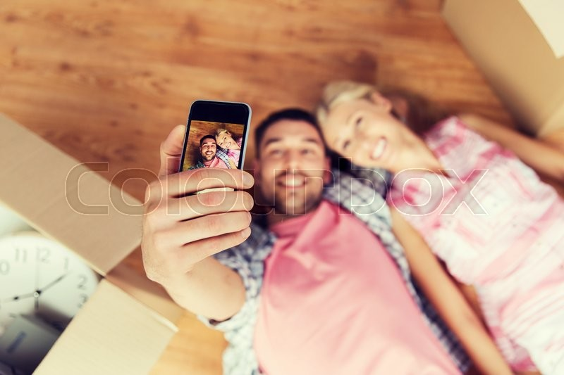 Stock image of 'new home, technology, people, repair and moving concept - happy couple taking selfie with smartphone and lying on floor among cardboard boxes at home'