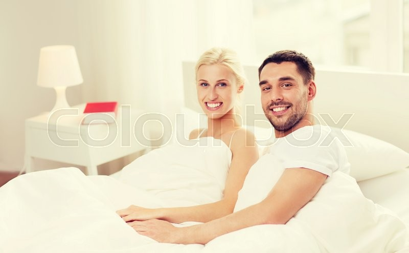Stock image of 'people, family, bedtime and happiness concept - happy couple lying in bed at home'