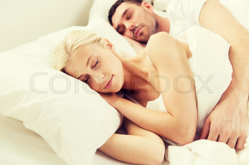 Stock image of 'people, rest, relationships and happiness concept - happy couple sleeping in bed at home'