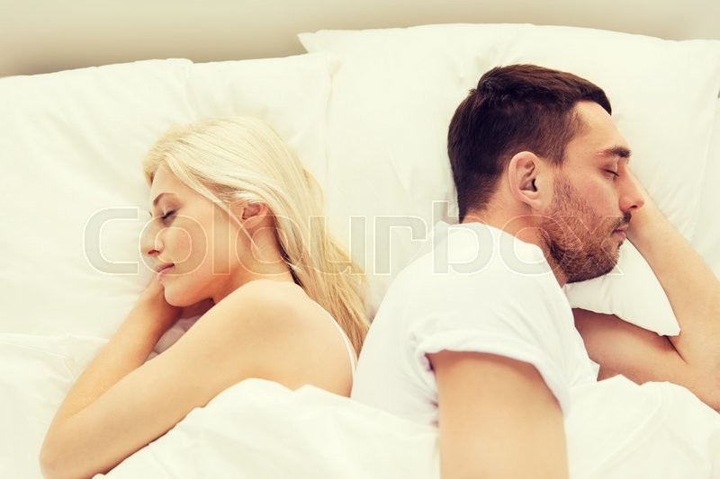 Stock image of 'people, rest, bedtime and family concept - couple sleeping back to back in bed at home'