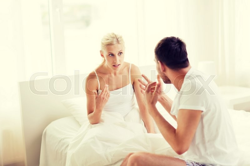 Stock image of 'people, relationship difficulties, conflict and family concept - unhappy couple having argument at bedroom'