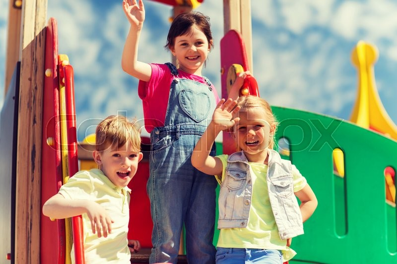 Stock image of 'summer, childhood, leisure, friendship and people concept - group of happy kids waving hands on children playground'