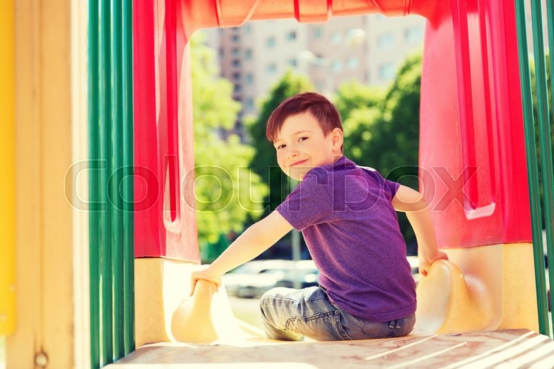 Stock image of 'summer, childhood, leisure and people concept - happy little boy on slide at children playground'