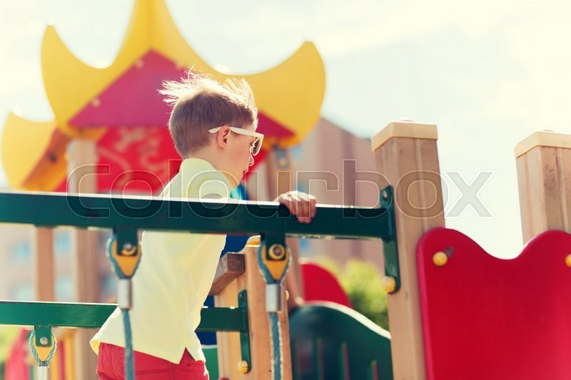 Stock image of 'summer, childhood, leisure and people concept - happy little boy on children playground climbing frame'
