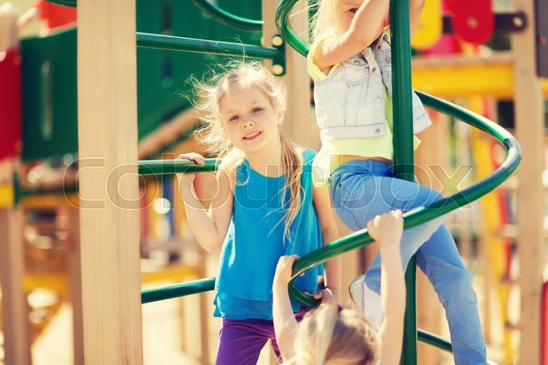 Stock image of 'summer, childhood, leisure, friendship and people concept - group of happy kids on children playground climbing frame'