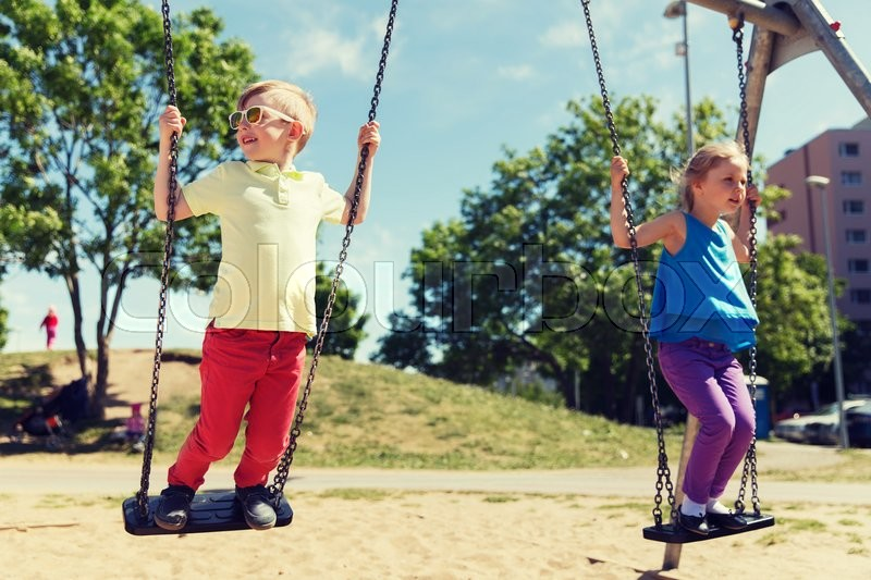 Stock image of 'summer, childhood, leisure, friendship and people concept - two happy kids swinging on swing at children playground'
