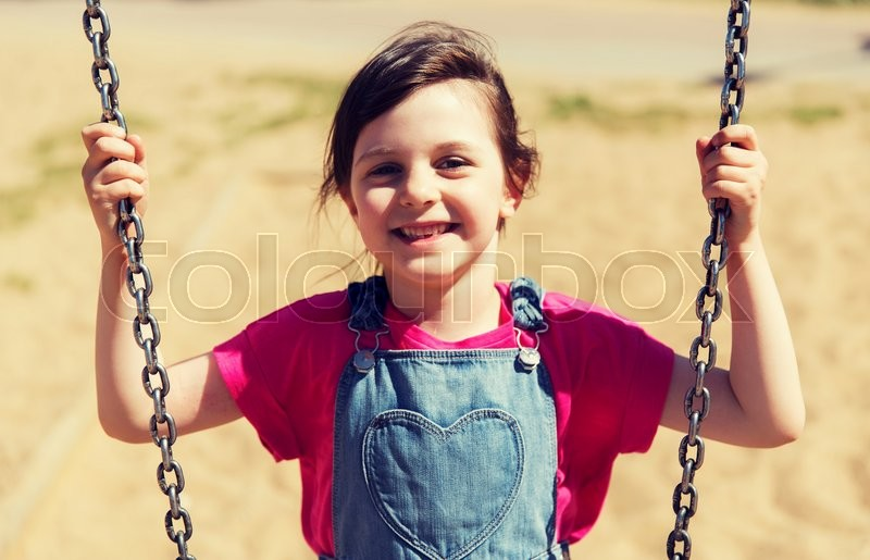 Stock image of 'summer, childhood, leisure, friendship and people concept - happy little girl swinging on swing at children playground'