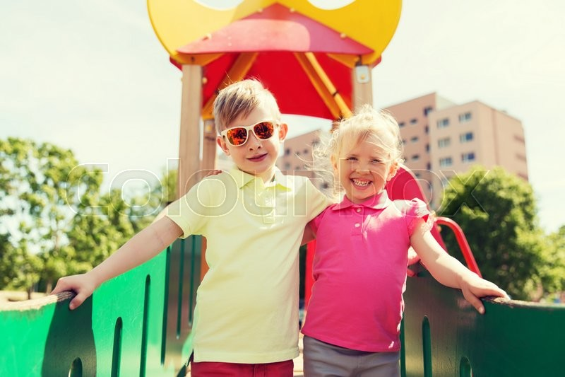 Stock image of 'summer, childhood, leisure, friendship and people concept - two happy kids hugging on children playground'