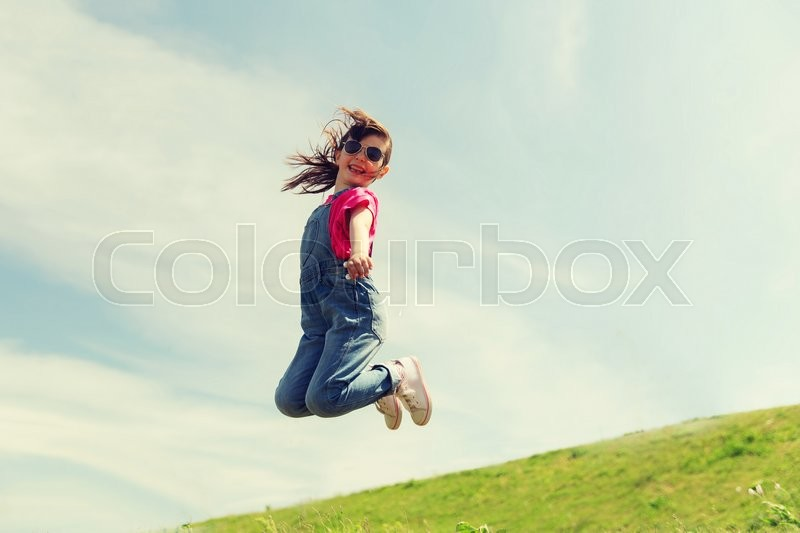 Stock image of 'summer, childhood, leisure and people concept - happy little girl jumping high over green field and blue sky outdoors'
