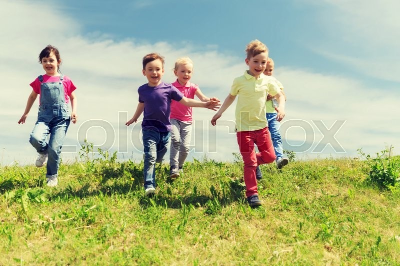 Stock image of 'summer, childhood, leisure and people concept - group of happy kids playing tag game and running on green field outdoors'