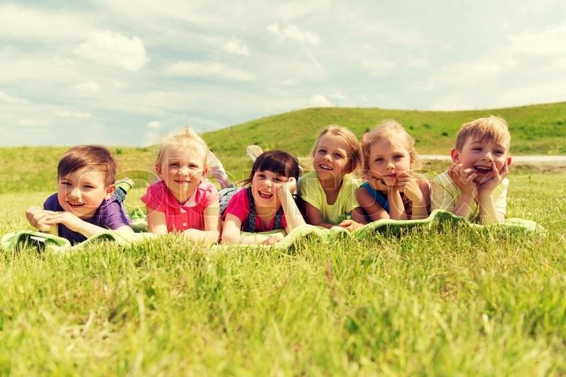 Stock image of 'summer, childhood, leisure and people concept - group of happy kids lying on blanket or cover outdoors'