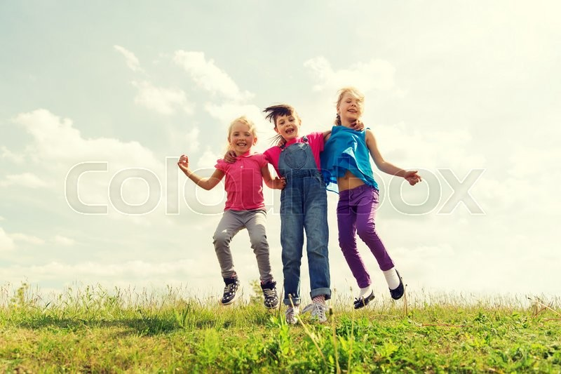 Stock image of 'summer, childhood, leisure and people concept - group of happy kids jumping high on green field outdoors'