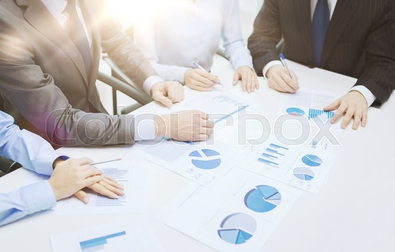 Stock image of 'business and office concept - close up of business team with chats and graphs in office'