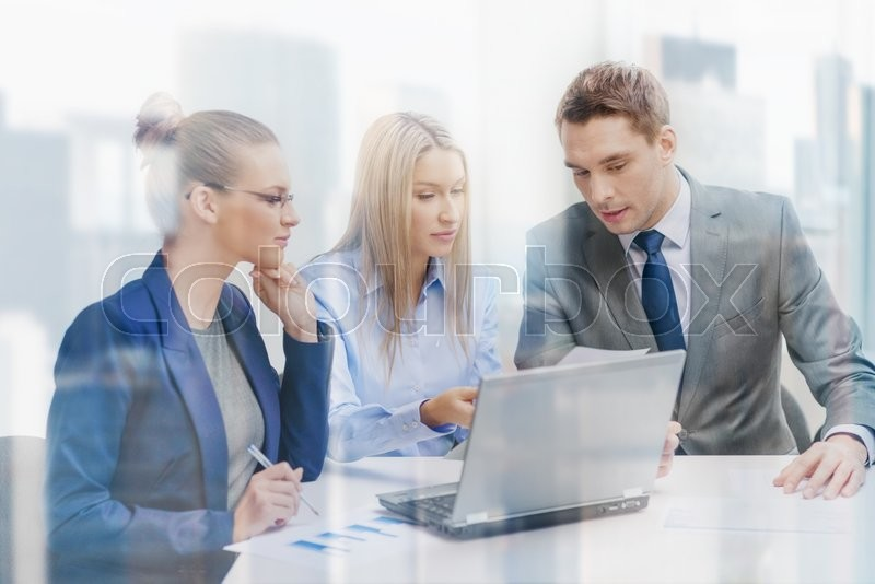 Stock image of 'business, technology and office concept - concentrated business team with laptop computers and documents having discussion in office'