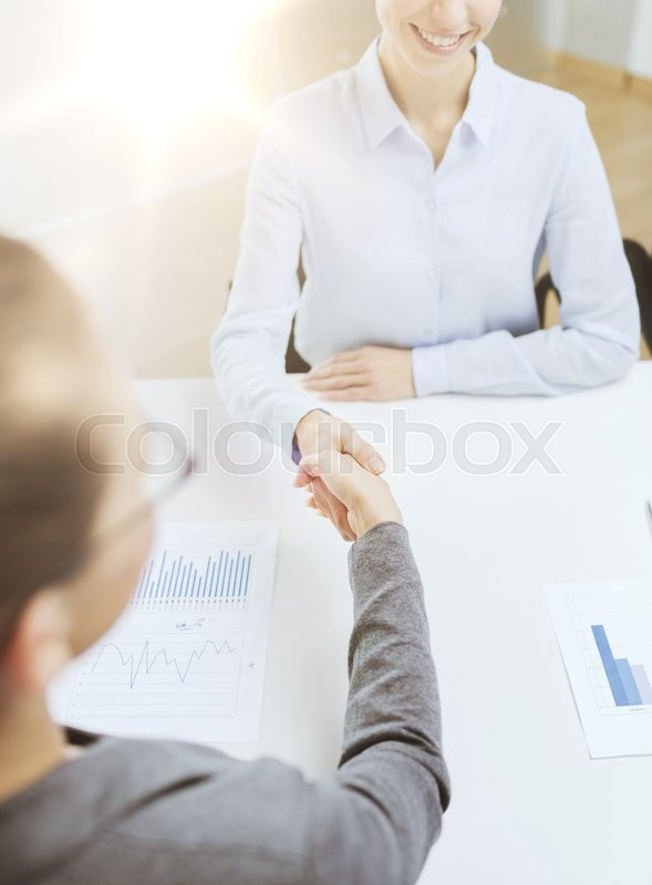 Stock image of 'business and office concept - two smiling businesswoman shaking hands in office'