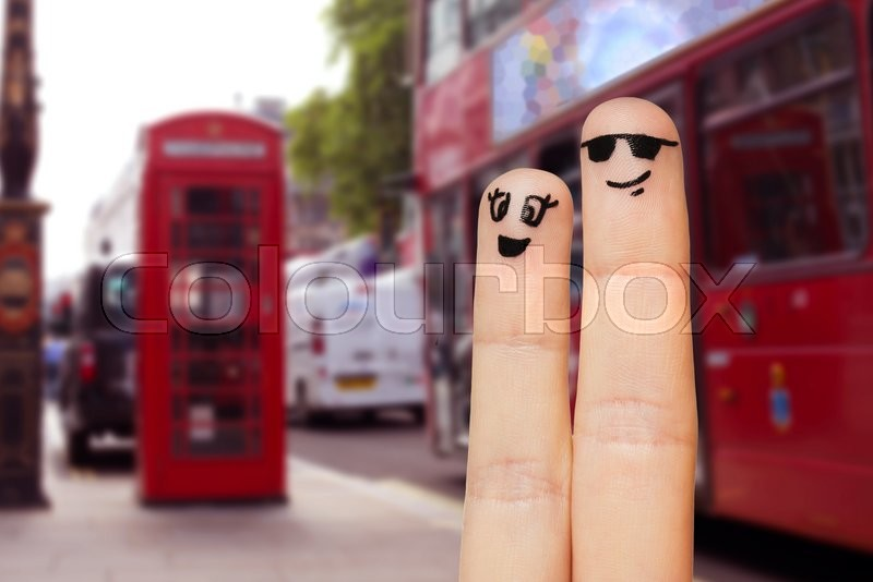 Stock image of 'family, couple, travel, tourism and body parts concept - close up of two fingers with smiley faces over london city street background'