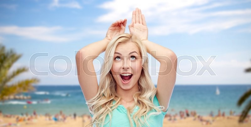 Stock image of 'fun, expressions, summer holidays, travel and people concept - happy smiling young woman making bunny ears over exotic tropical beach with palm trees and sea background'