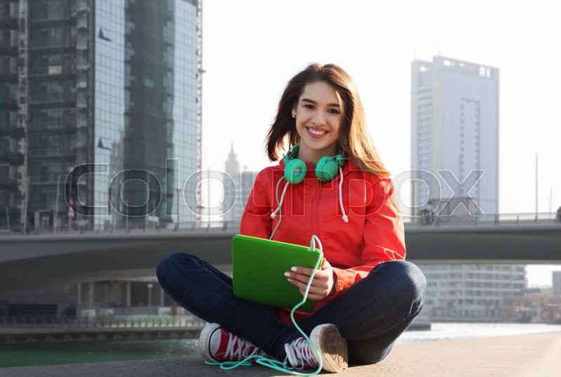Stock image of 'technology, travel, tourism, music and people concept - smiling young woman or teenage girl with tablet pc computer and headphones over dubai city street background'