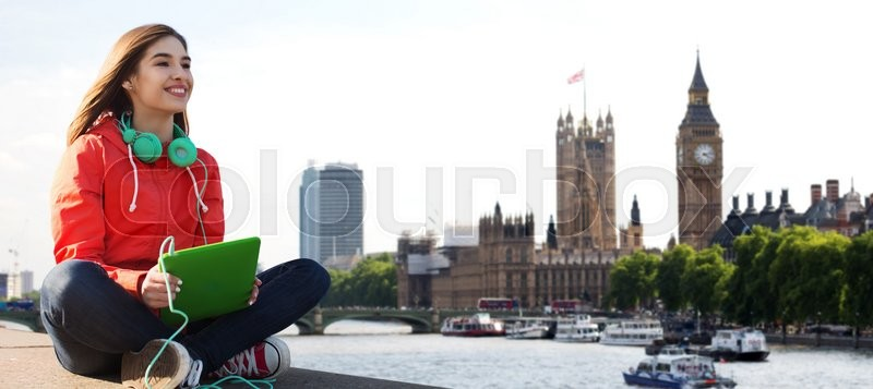 Stock image of 'technology, travel, tourism, music and people concept - smiling young woman or teenage girl with tablet pc computer and headphones over london city and big ben tower background'