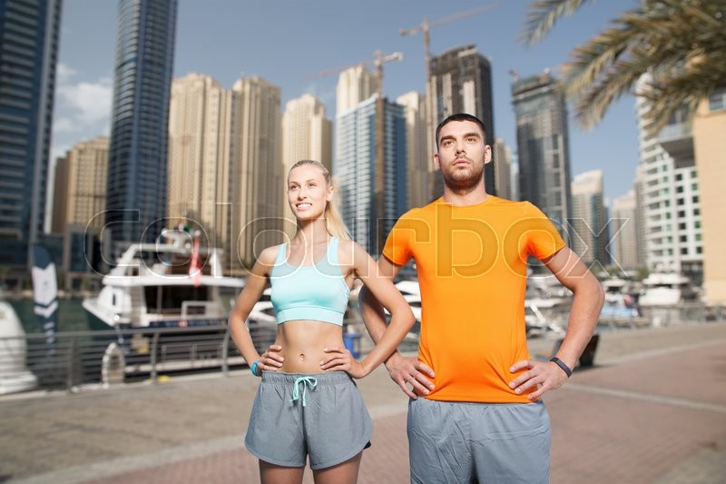 Stock image of 'fitness, sport, friendship and healthy lifestyle concept - happy couple exercising over dubai city street background'
