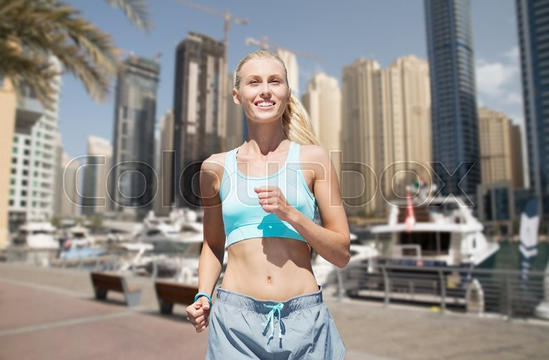 Stock image of 'fitness, sport, friendship and healthy lifestyle concept - smiling young woman running or jogging over dubai city street background'