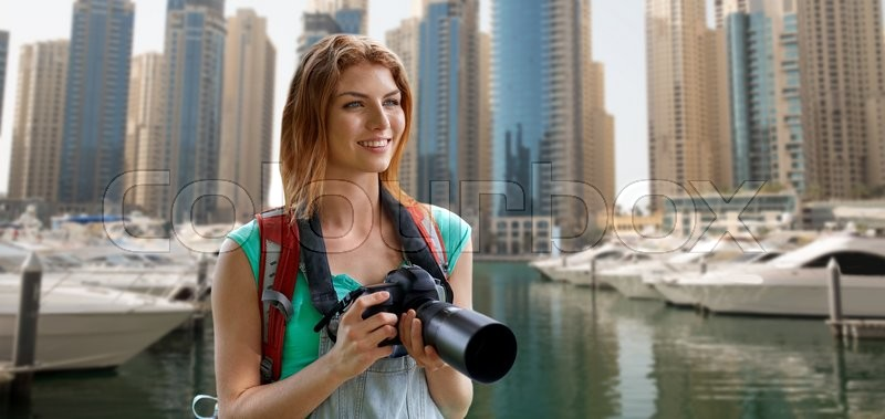 Stock image of 'adventure, travel, tourism, hike and people concept - happy young woman with backpack and camera photographing over dubai city and harbor with boats background'