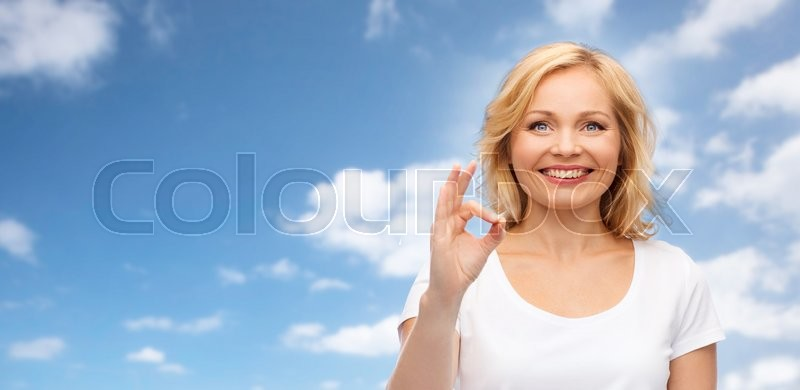 Stock image of 'gesture, advertisement and people concept - smiling woman in blank white t-shirt showing ok hand sign over blue sky and clouds background'