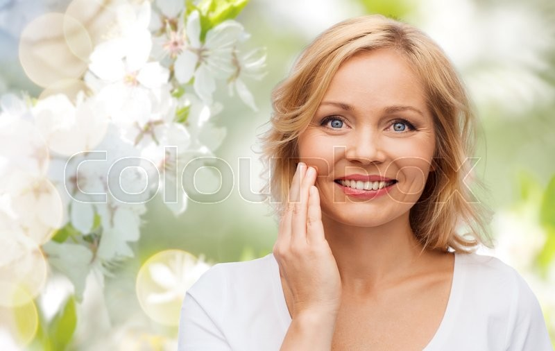 Stock image of 'beauty, people and skincare concept - smiling woman in white shirt touching face over natural spring cherry blossom background'