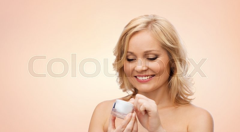 Stock image of 'beauty, people, skincare and cosmetics concept - happy woman with cream jar over beige background'