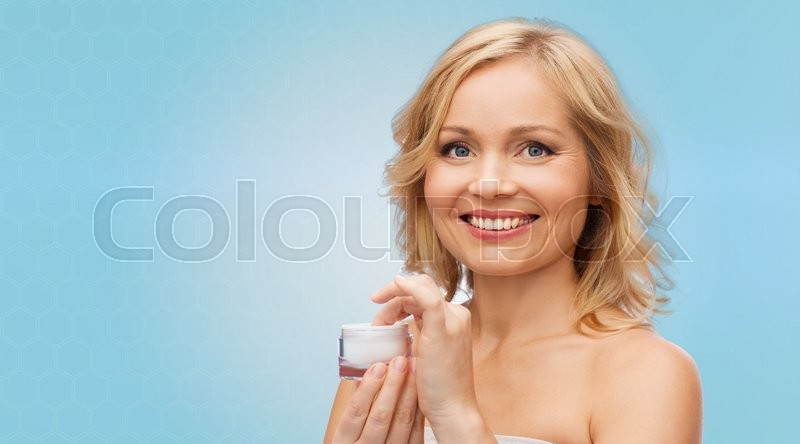 Stock image of 'beauty, people, skincare and cosmetics concept - happy woman with cream jar over blue background'