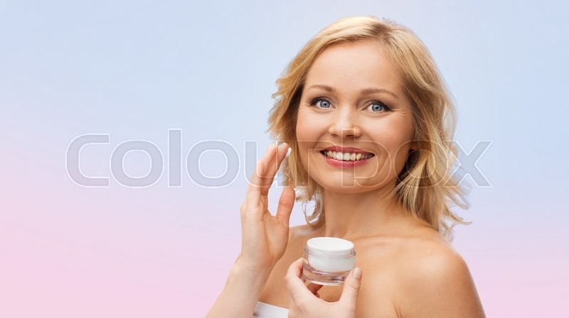 Stock image of 'beauty, people, skincare and cosmetics concept - happy woman applying cream to her face over rose quartz and serenity gradient background'