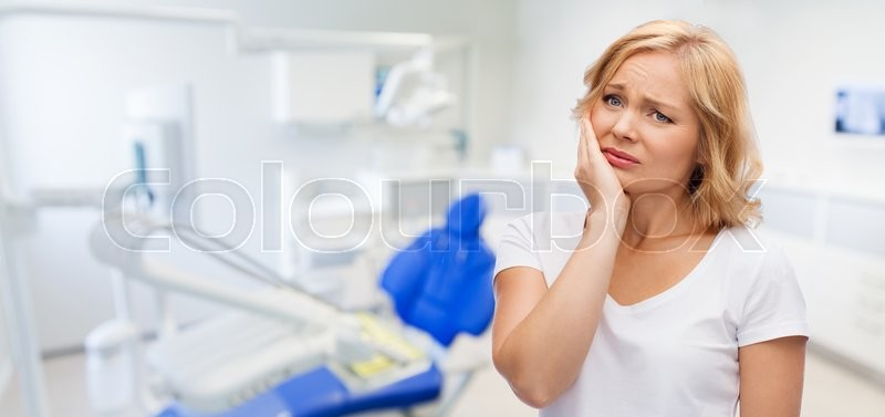 Stock image of 'people, healthcare, dentistry and problem concept - unhappy woman suffering toothache over dental office background'