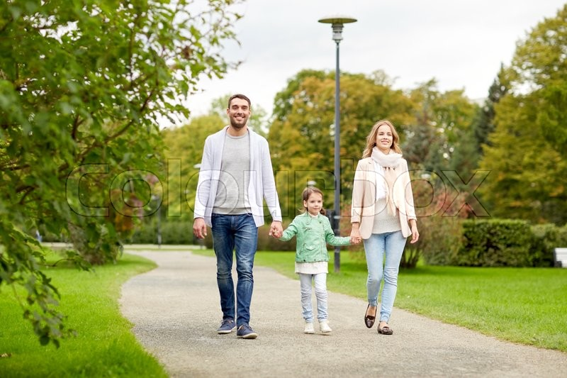 Stock image of 'family, parenthood, adoption and people concept - happy mother, father and little girl walking in summer park'