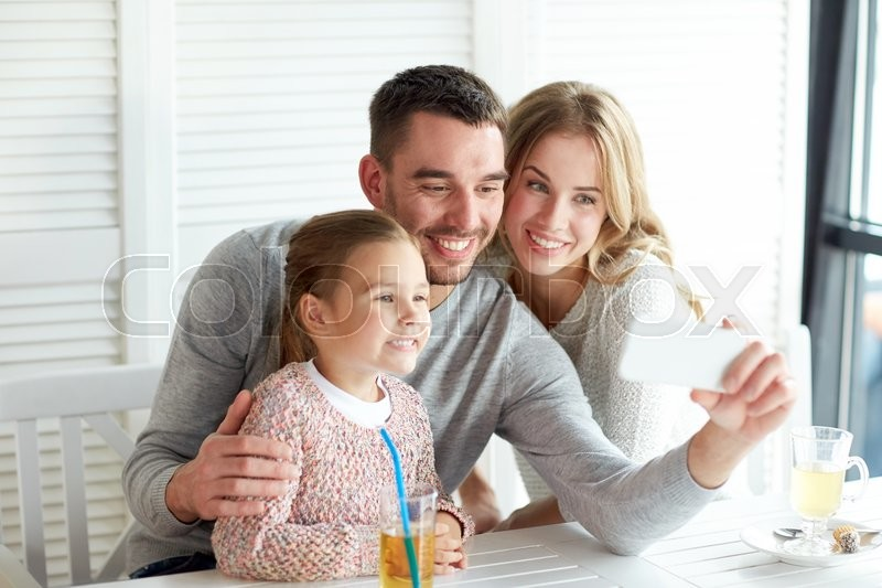 Stock image of 'family, parenthood, technology and people concept - happy mother, father and little girl having dinner and taking selfie by smartphone at restaurant'