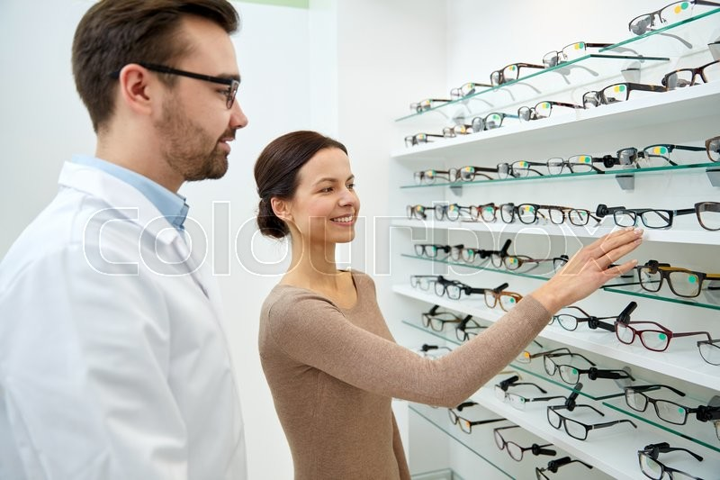 Stock image of 'health care, people, eyesight and vision concept - happy woman choosing and showing glasses to optician at optics store'
