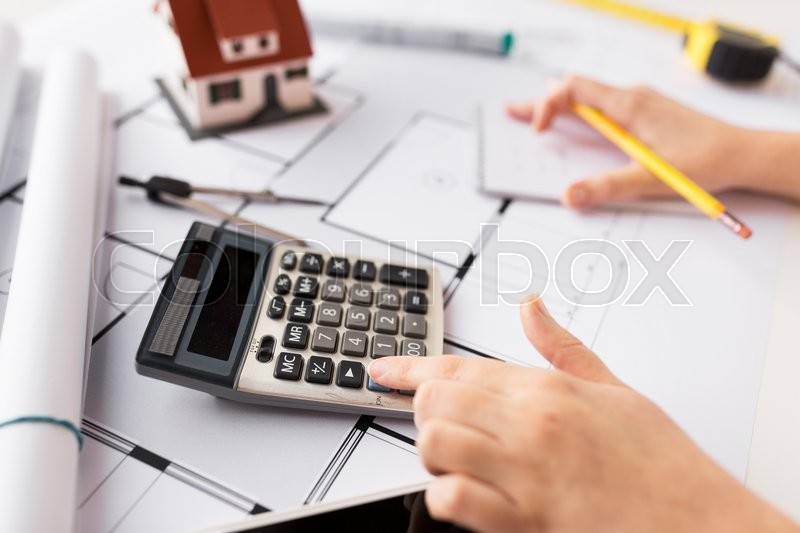 Stock image of 'business, architecture, building, construction and people concept - close up of architect hand with blueprint counting on calculator'