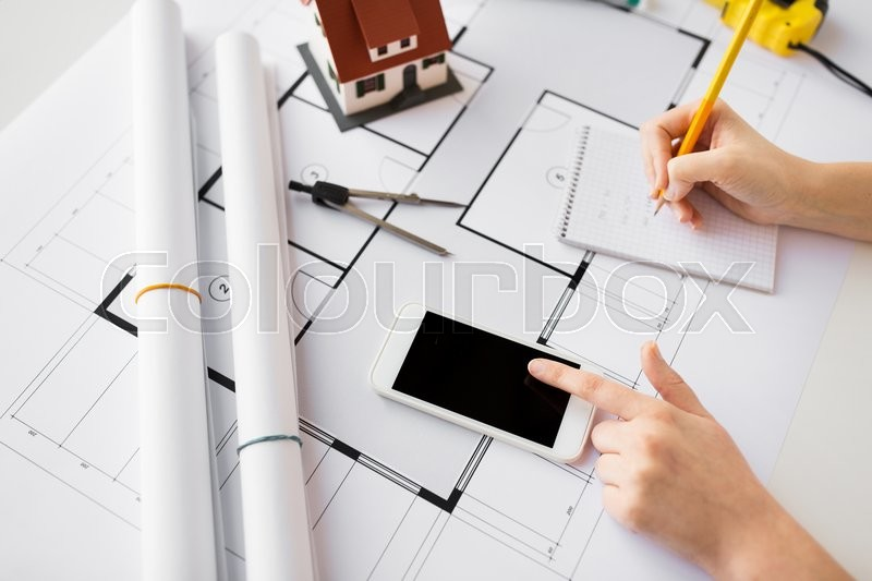 Stock image of 'business, architecture, building, construction and people concept - close up of architect hand with living house blueprint and smarphone writing to notebook'