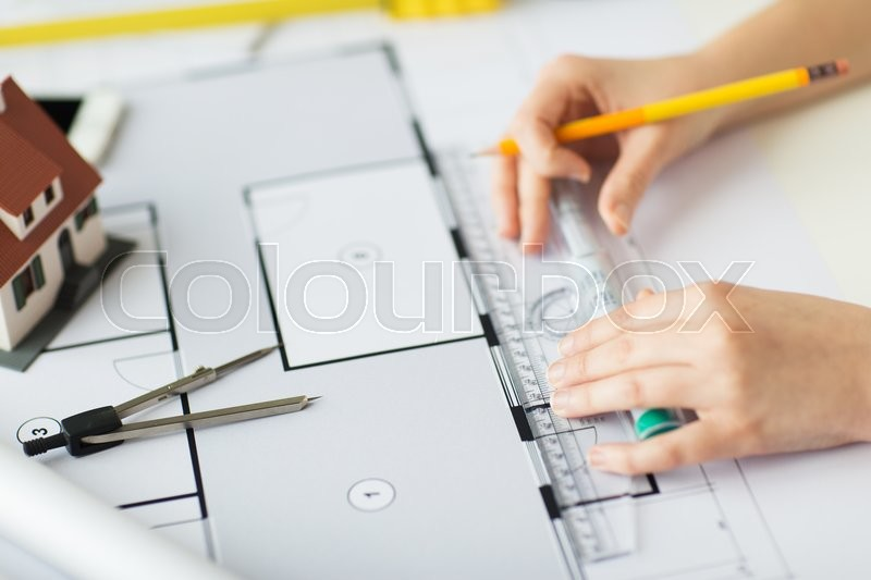 Stock image of 'business, architecture, building, construction and people concept - close up of architect hands with ruler and pencil measuring living house blueprint'