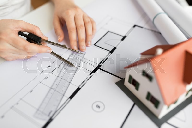 Stock image of 'business, architecture, building, construction and people concept - close up of architect hands with compass and ruler measuring living house blueprint'