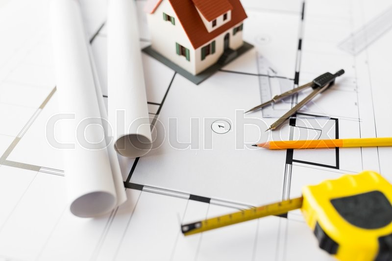 Stock image of 'architecture, building, construction, real estate and home concept - close up of blueprint with living house model and tools'
