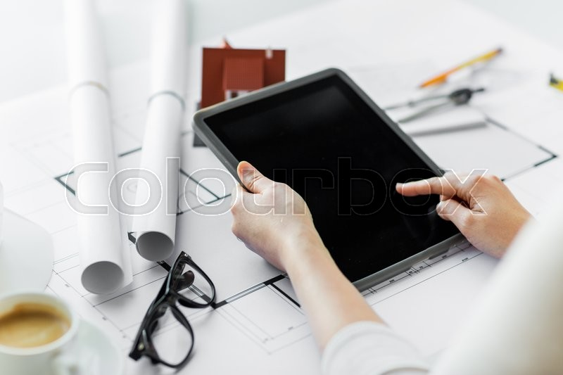 Stock image of 'business, architecture, building, construction and people concept - close up of architect hand with living house blueprint and tablet pc computer'