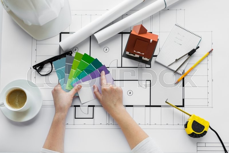 Stock image of 'business, architecture, building, construction and people concept - close up of designer hands with color palette and house blueprint'