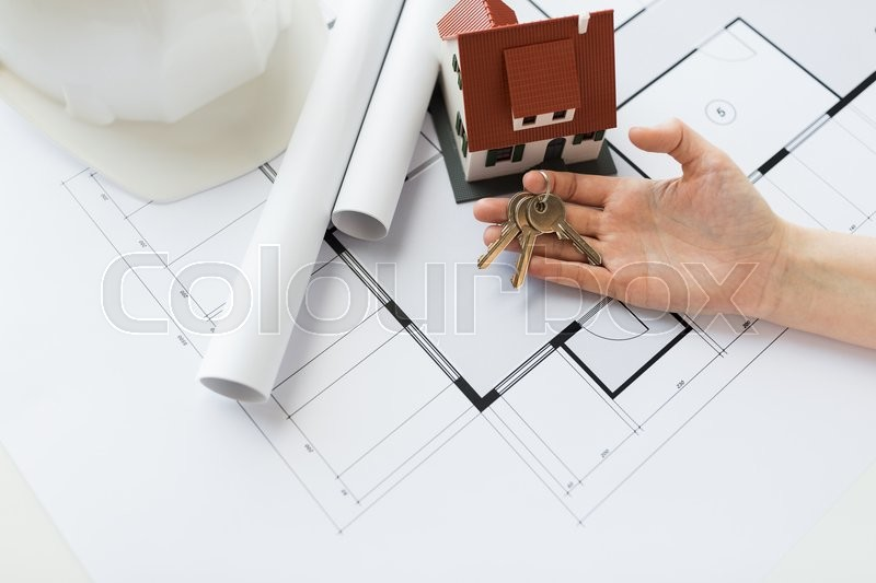 Stock image of 'architecture, building, construction, real estate and home concept - hand with house keys and blueprint'