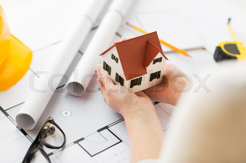 Stock image of 'architecture, building, construction, real estate and people concept - close up of architect hands holding living house model above blueprint on table'
