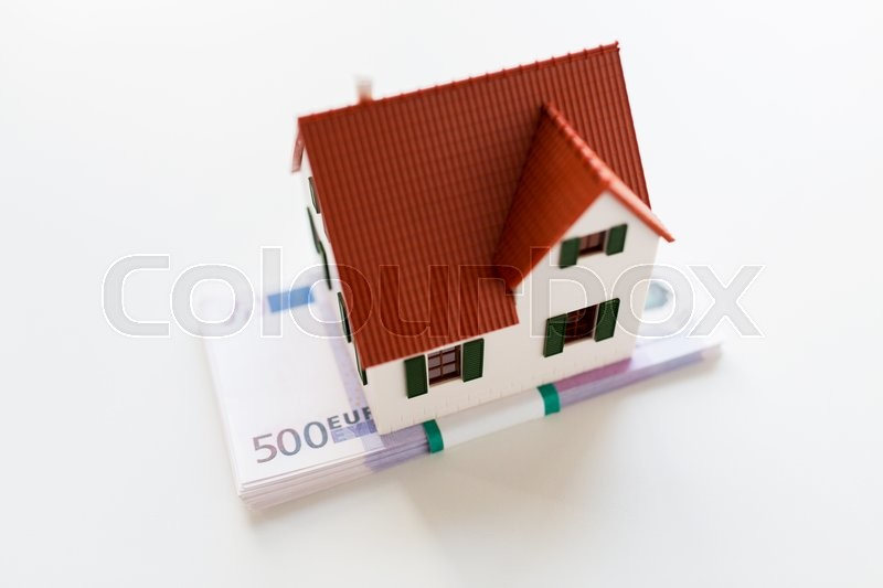Stock image of 'building, mortgage, investment, real estate and property concept - close up of home or house model and money'