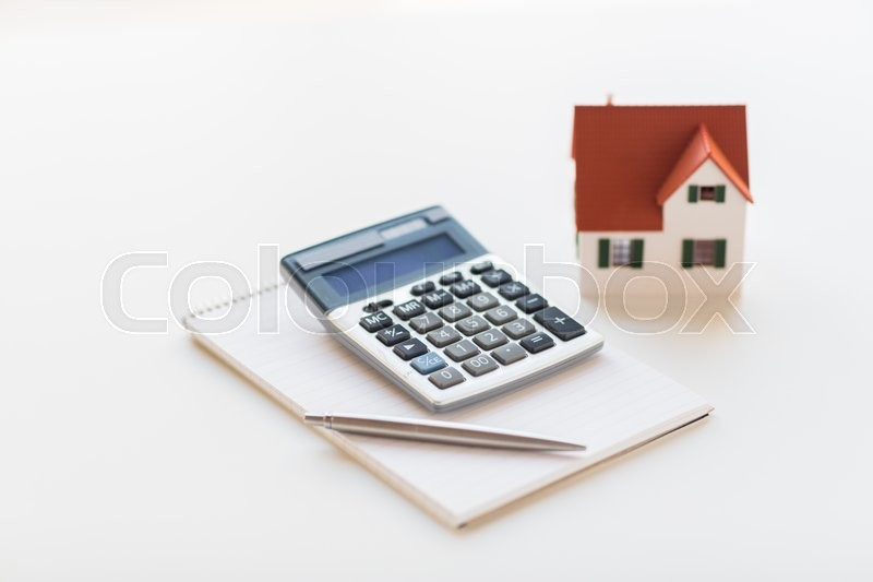 Stock image of 'building, mortgage, real estate and property concept - close up of home model, house keys and notebook with pen'