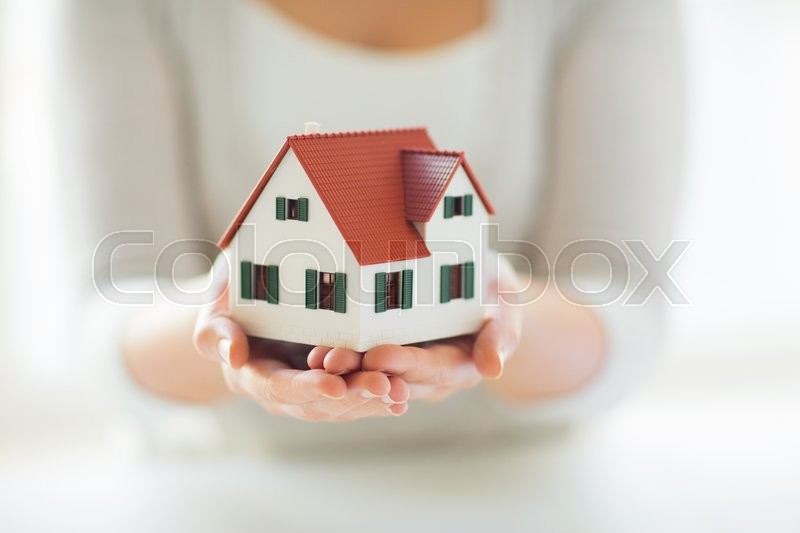 Stock image of 'architecture, building, construction, real estate and property concept - close up of hands holding house or home model'