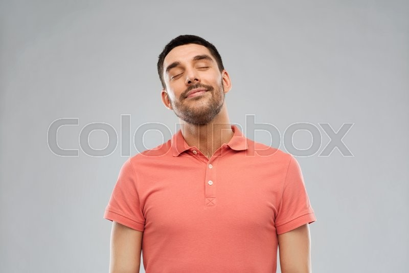 Stock image of 'emotion and people concept - laughing man in polo t-shirt over gray background'