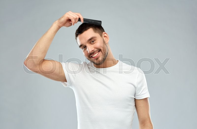 Stock image of 'beauty, grooming and people concept - smiling young man brushing hair with comb over gray background'